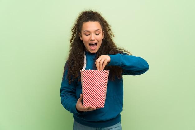 Menina adolescente sobre parede verde surpreendeu e comendo pipocas