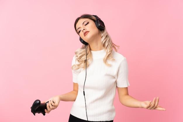 Menina adolescente sobre rosa isolado jogando em videogame