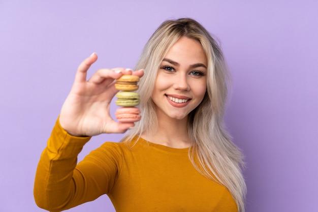Menina adolescente sobre roxo isolado segurando macarons franceses coloridos e com expressão feliz