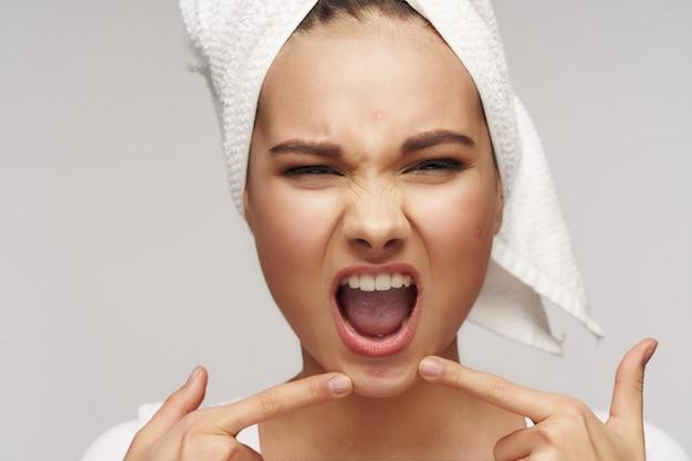 Menina adolescente soprando uma espinha no queixo.