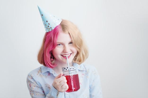 Menina adolescente sorridente com chapéu de aniversário