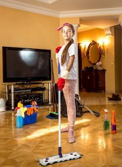 Menina adolescente sorridente limpando o chão da sala de estar com cotonete