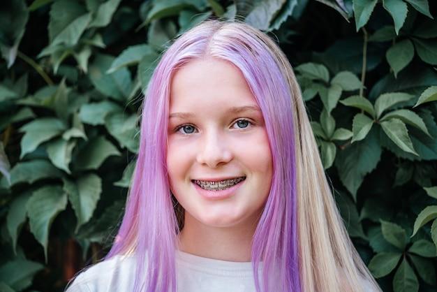 Menina adolescente sorridente usando aparelho dentário, linda garota caucasiana de cabelo rosa usando aparelho ortodôntico