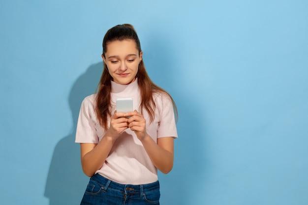 Menina adolescente sorrindo, usando smartphone