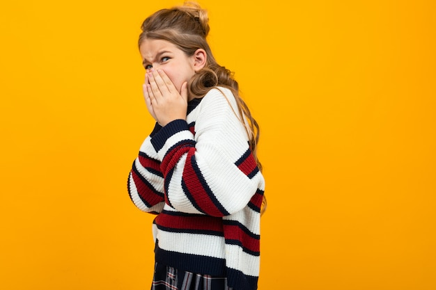 Menina adolescente surpreendida na camisola listrada casual cobriu a boca com as mãos onn laranja com espaço de cópia