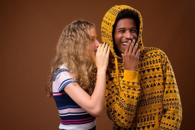 Menina adolescente sussurrando para um homem africano feliz que está rindo