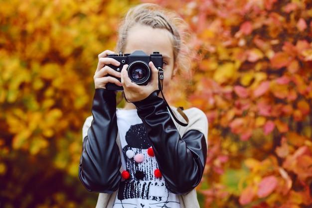 Menina adolescente tirando fotos com uma câmera fotográfica antiga