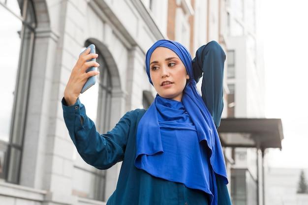 Menina adolescente tirando uma selfie lá fora