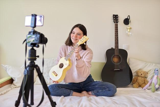 Menina adolescente toca música no ukulele, aprendizagem online e bate-papo com seguidores. blog musical de adolescentes, vlog, canal, tecnologia moderna, conceito jovem