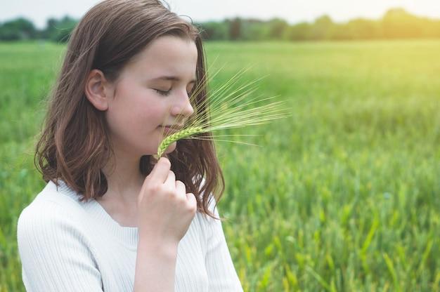 Menina adolescente tocando as mãos com trigo verde no campo