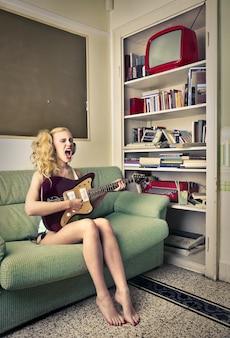 Menina adolescente, tocando, um violão, casa
