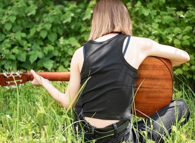 Menina adolescente tocando violão no parque vista traseira
