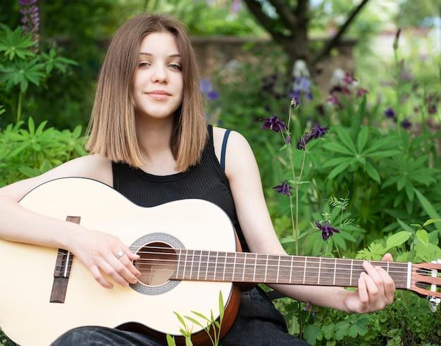 Menina adolescente tocando violão no parque