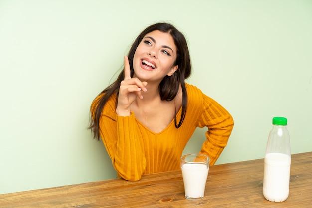 Menina adolescente tomando café da manhã leite e pensando