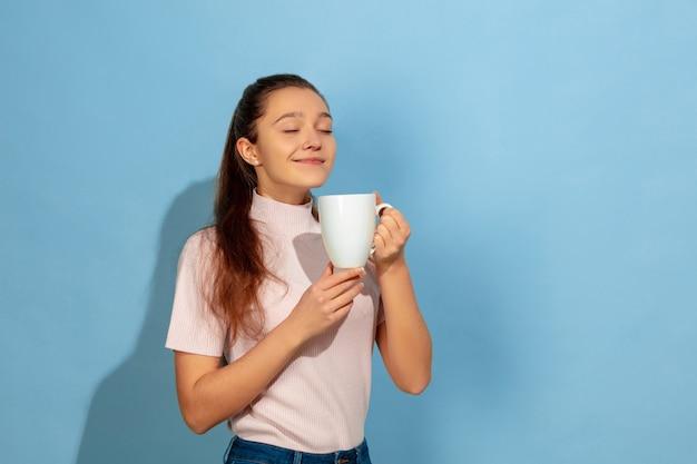 Menina adolescente tomando café