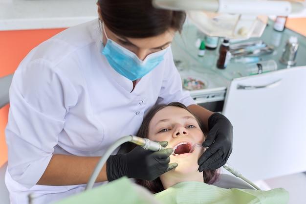 Menina adolescente tratando os dentes no consultório dentista, consulta do ortodontista. odontologia, dentes saudáveis, medicina e conceito de saúde