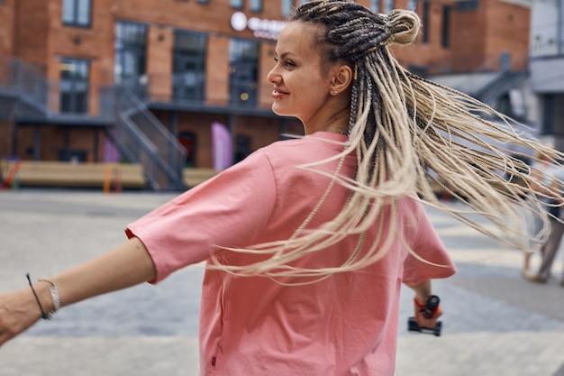 Menina adolescente travessa com dreadlocks girando alegremente na rua da cidade grande contra o ...