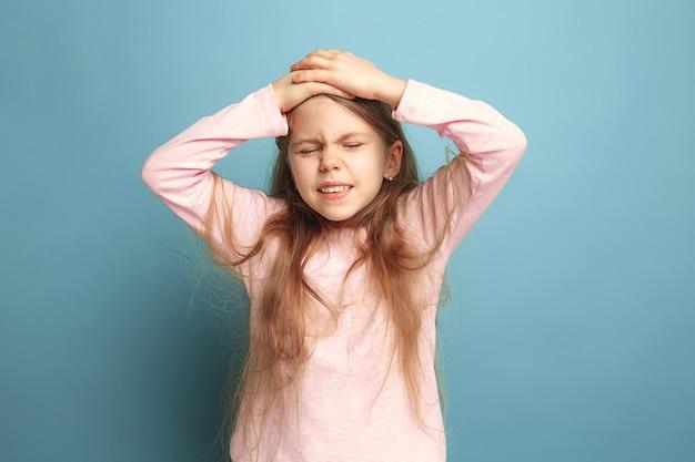 Menina adolescente triste com dor de cabeça ou dor em um fundo azul do estúdio. expressões faciais e conceito de emoções de pessoas.