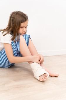 Menina adolescente triste com gesso ortopédico no pé, sentada no chão. cirurgia para corrigir a deformidade do pé em crianças. pacientes com pequena mobilidade.