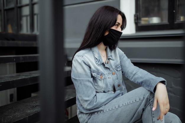 Menina adolescente triste na máscara médica atrás das grades. as escolas são colocadas em quarentena devido a doenças, epidemias. pandemia do coronavírus. covid 19.