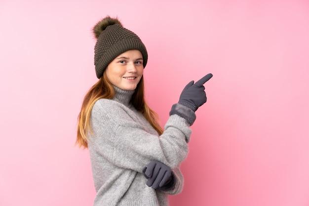 Menina adolescente ucraniana com chapéu de inverno sobre o dedo apontando rosa isolado para o lado