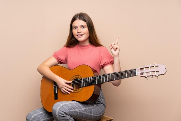 Menina adolescente ucraniana com guitarra apontando para cima uma ótima idéia