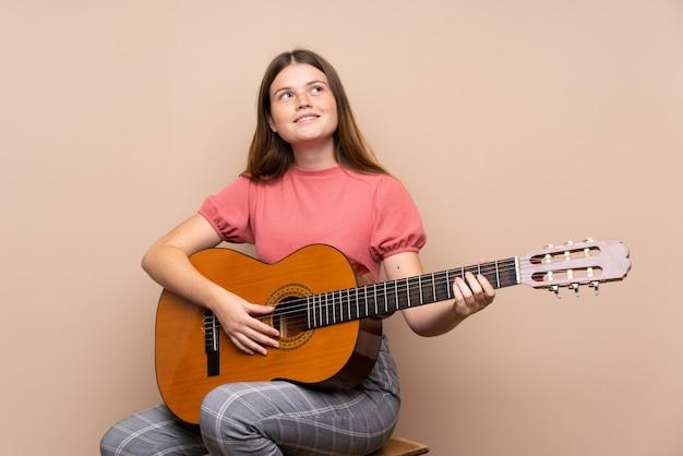 Menina adolescente ucraniana com guitarra sobre isolado olhando para cima enquanto sorrindo