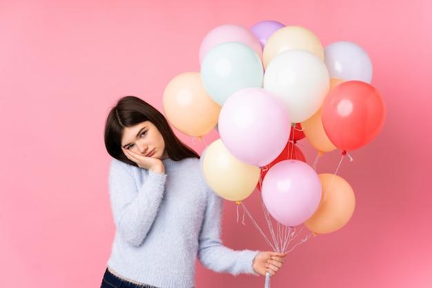 Menina adolescente ucraniana segurando muitos balões sobre parede rosa infeliz e frustrada