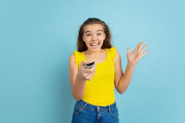 Menina adolescente usando controle remoto da tv