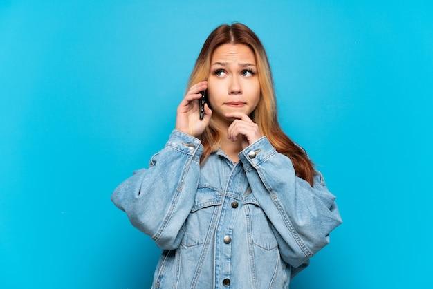 Menina adolescente usando telefone celular sobre fundo isolado, tendo dúvidas e pensando