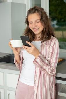 Menina adolescente, usando, um, smartphone, cozinha