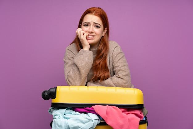 Menina adolescente viajante com uma mala cheia de roupas nervosas e assustadas