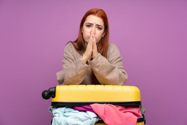 Menina adolescente viajante com uma mala cheia de roupas suplicando