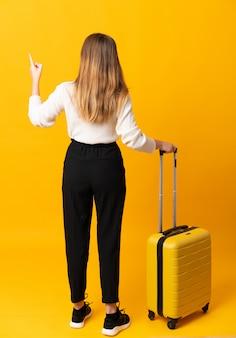 Menina adolescente viajante sobre parede amarela isolada