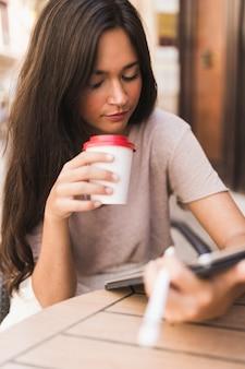Menina adolescente, xícara takeaway café, olhar, tablete digital