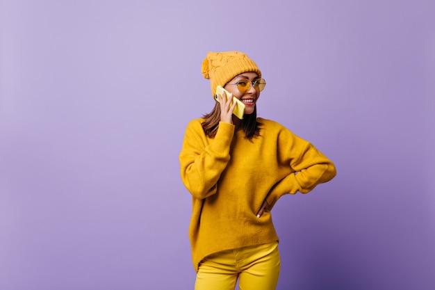 Menina adora a cor laranja e posando para o novo snapportrait com roupa elegante. modelo falando no telefone amarelo, sorrindo amigável