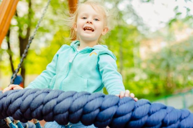 Menina adorável 4 anos velha que tem o divertimento em um balanço da corda redonda em um campo de jogos no dia de verão.