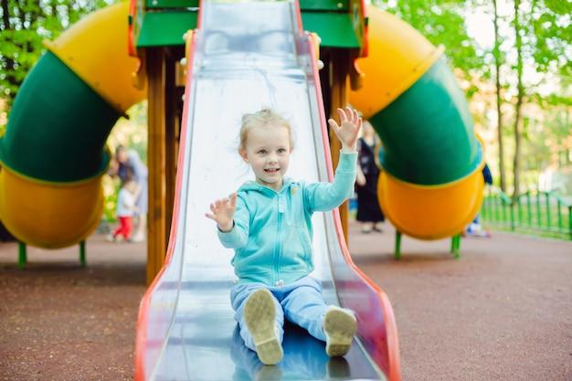 Menina adorável 4 anos velha que tem o divertimento em uma corrediça em um campo de jogos no dia de verão.