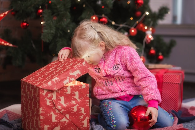 Menina adorável abrindo um presente de natal mágico perto de uma árvore de natal em uma sala de estar aconchegante