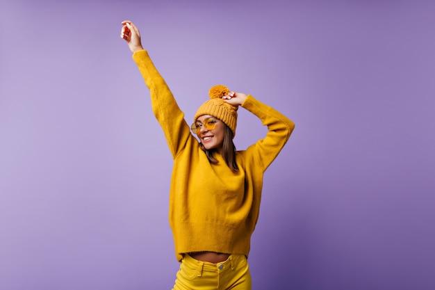 Menina adorável alegre move as mãos. snapportrait de um aluno ativo em jeans brilhantes