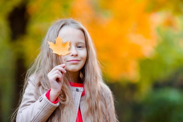 Menina adorável ao ar livre no belo dia quente no parque do outono com a folha amarela em queda