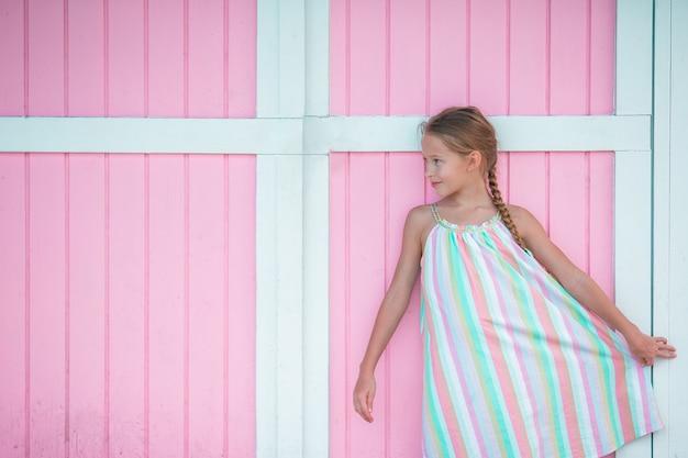 Menina adorável ao ar livre perto da casa cor-de-rosa colorida tradicional do cararibe
