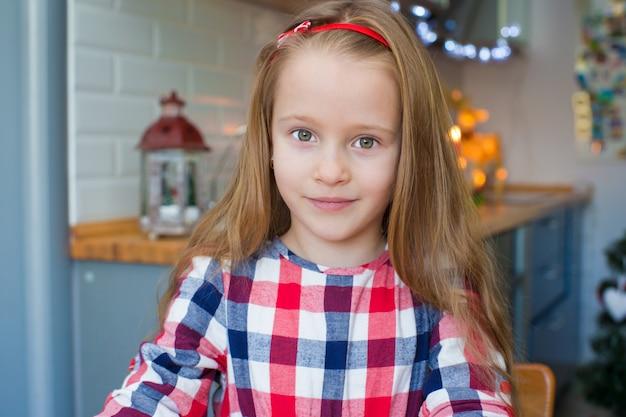 Menina adorável assando biscoitos de natal em casa