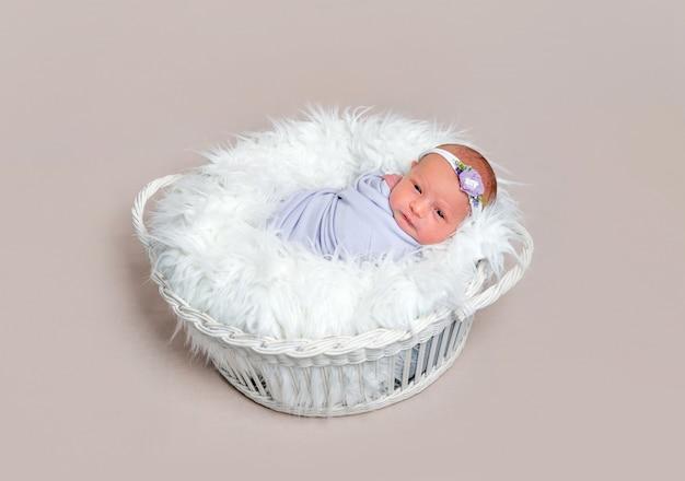 Menina adorável bebê recém-nascido envolto em um casulo roxo