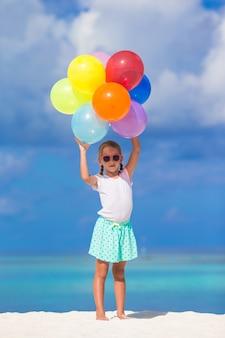 Menina adorável brincando com balões na praia