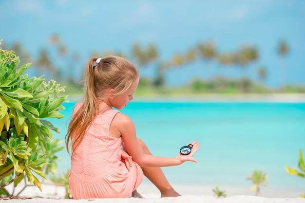 Menina adorável brincando com brinquedos de praia durante as férias tropicais