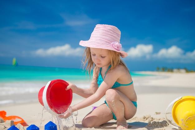 Menina adorável brincando com brinquedos em férias de praia