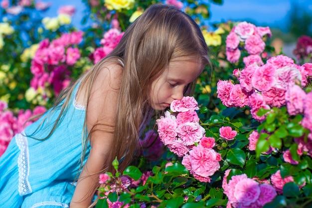 Menina adorável cheirando flores coloridas no dia de verão