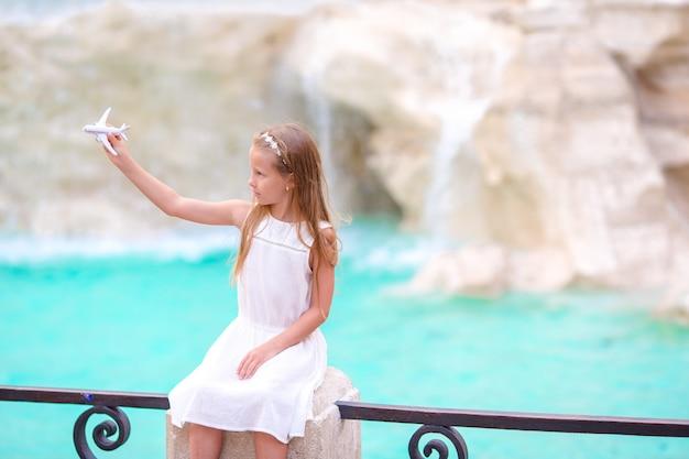 Menina adorável com a fonte do trevi do fundo do avião do brinquedo, roma, itália.