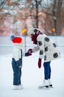 Menina adorável com a mãe dela patinar na pista de gelo
